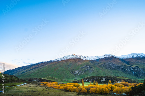 Stunning landscape view of green grass field and snow mountain in autumn. Diamond lake track, Wanaka, New Zealand.