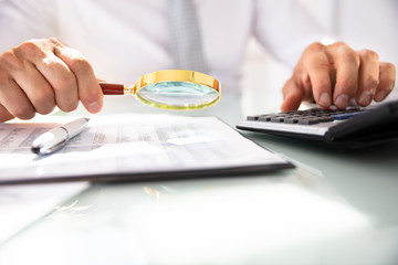 Fototapeta Businessman Analyzing Financial Report With Magnifying Glass