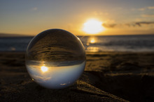 Sunset On Sand Through Glass Ball With Ocean