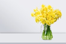 Narcissus Flowers In Vase On Wooden Background
