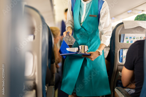 Photo Flight attendant serving drinks to passengers on board.