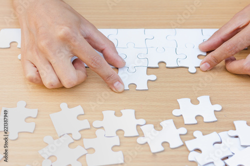 Fototapety, obrazy: Hands of diverse people assembling jigsaw puzzle, team put pieces together searching for right match, help support in teamwork to find common solution concept