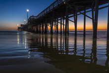 Sun Setting At Dusk Behind The Newport Beach Pier California