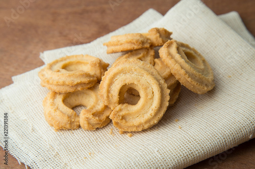 Deurstickers Koekjes Butter cookies on white linen on wooden table.