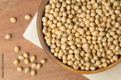 Soybeans in wooden bowl putting on linen and wooden background.