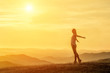 Happy woman with open arms stay on the peak of the mountain beautiful sunset background