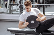 canvas print picture Muscular guy in white t-shirt doing sit ups at gym. Young athlete doing stomach workout in modern fitness studio.