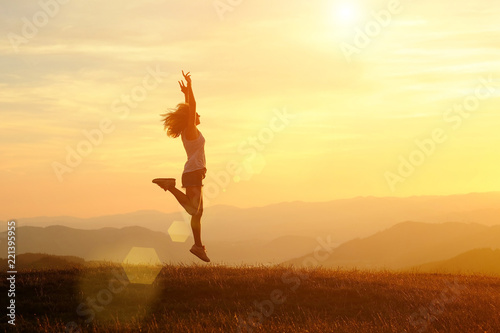 Foto auf Leinwand Gelb Schwefelsäure Happy woman with open arms jumping on the peak of the mountain beautiful sunset background
