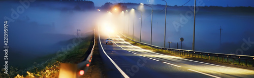 Photo sur Aluminium Bleu nuit view of car in traffic jam / rear view of the landscape from window in car, road with cars, lights and the legs of the cars night view