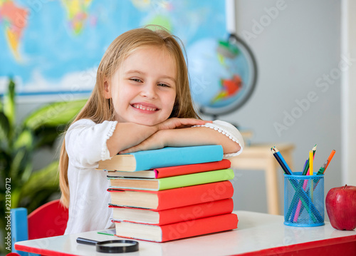 Foto Little smiling blond girl holding hands on the books in the school classroom