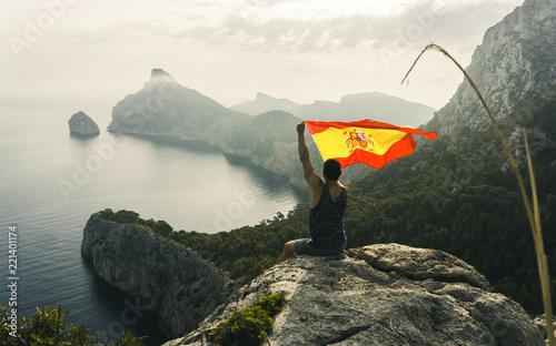 Poster Kaki Lonely man hiker sitting alone in his hand has a flag of spain on the rocky coast and enjoying sunset. View over rocky cliff to free ocean. Mallorca landscape and view to Cape Formentor