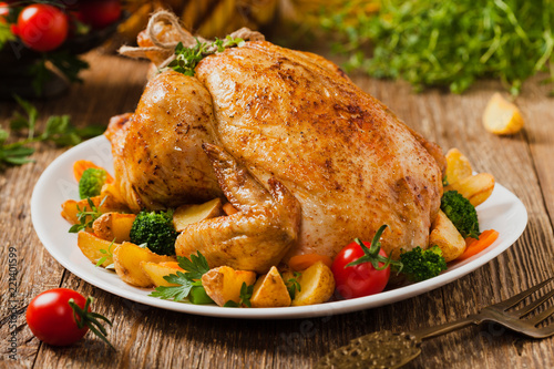 Roast chicken whole. Served on a plate with vegetables and baked potatoes.