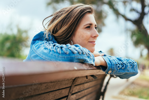 Fotografie, Obraz  Young woman sitting on a bench daydreaming