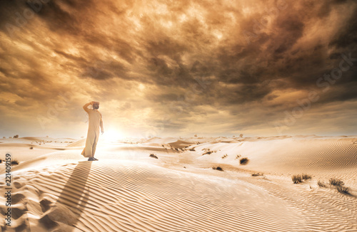 obraz dibond Man wearing traditional uae clothes spending time in the desert