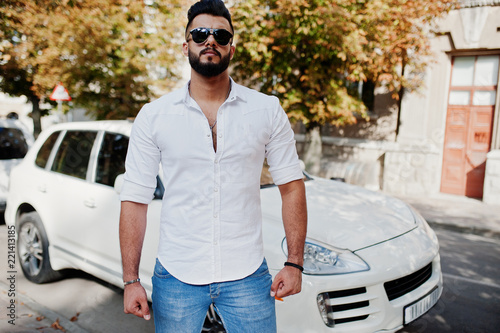 Photo Stylish tall arabian man model in white shirt, jeans and sunglasses posed at street of city