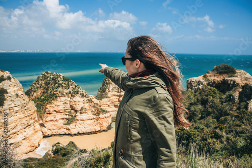 Foto  A tourist girl is pointing a hand at the beautiful view of the Atlantic Ocean off the coast of Portugal