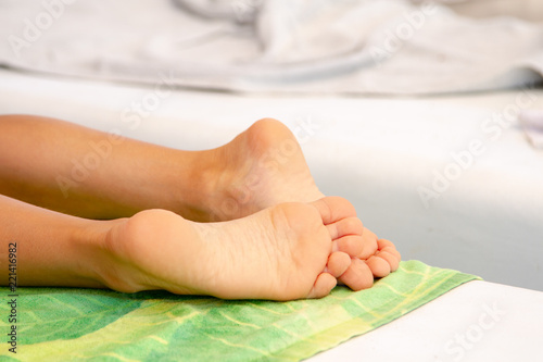 Fotografija Child's feet on a colored towel sunbathe on the beach sunbed