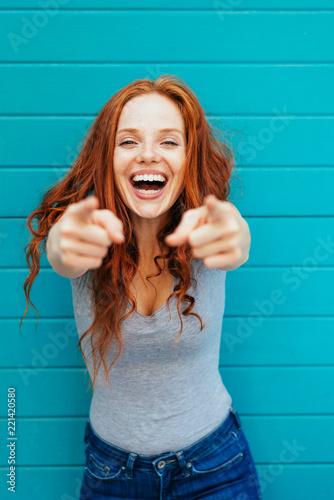 Vivacious laughing woman pointing at camera