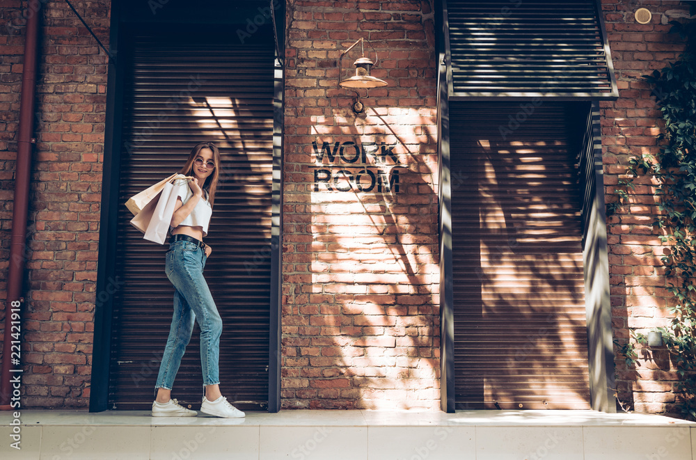 Fototapety, obrazy: Fashionable dressed young woman with shopping bags posing near brown metal shutters background.