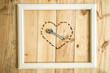 Viejo marco blanco vintage con herramientas variadas con forma de corazón sobre fondo de madera