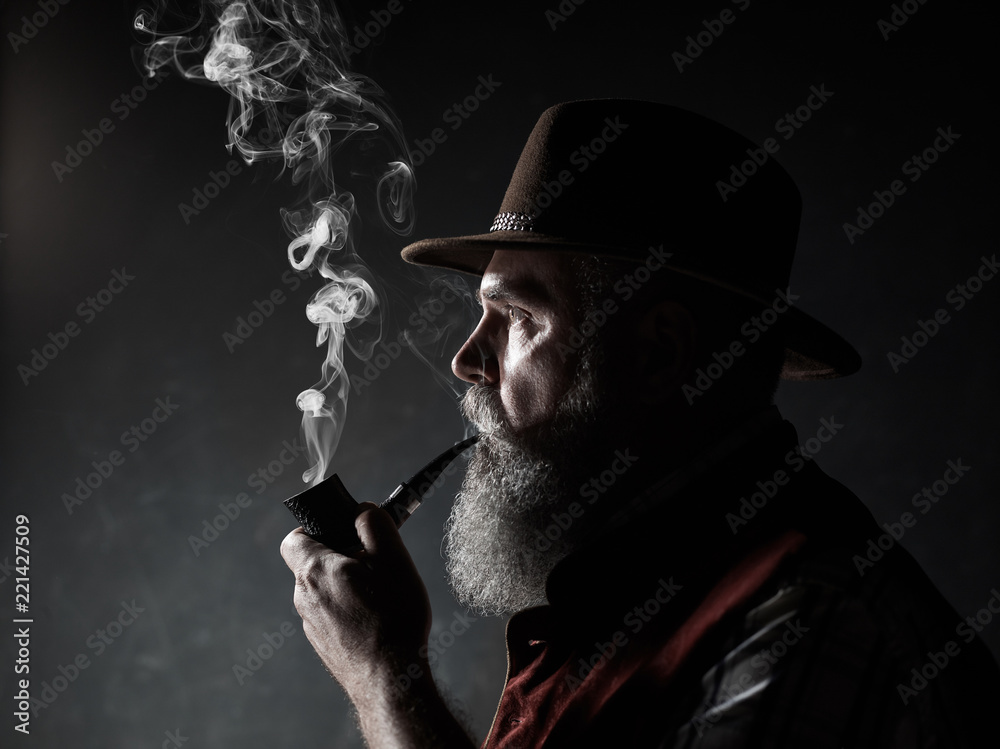Fototapeta dramatic portrait of senior man in hat smoking tobacco pipe. Profile view of Austrian, Tyrolean, Bavarian old man