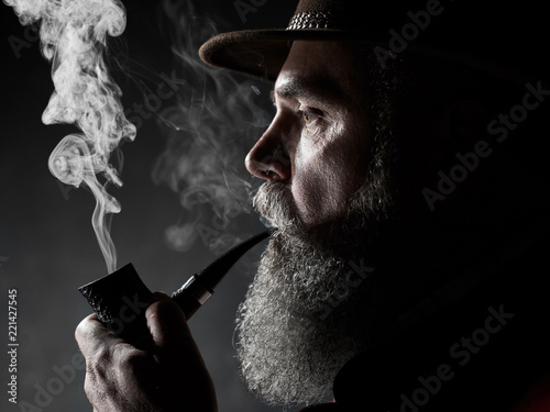 Obraz dramatic portrait of senior man in hat smoking tobacco pipe. Profile view of Austrian, Tyrolean, Bavarian old man - fototapety do salonu
