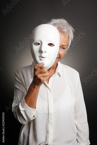 Photo  happy smiling playful mature woman peeking from behind mask