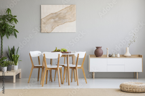 Fotografiet Real photo of Scandi dining room interior with vases on cupboard, chairs standin