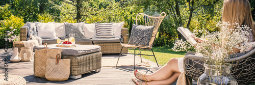 Photo Woman reading book on patio with rattan table, chair and sofa in the garden during summer