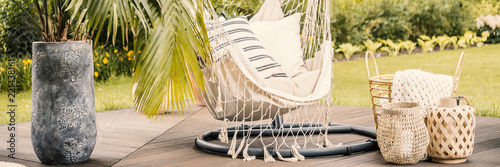 Photo  Hanging chair between lanterns and palm in stone vase on the terrace during spring