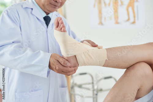 Unrecognizable adult doctor wrapping clean bandage carefully around foot and ank Canvas Print
