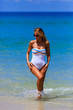 Model in white swimsuit walking at the beach