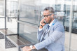 black man businessman in a business suit, expensive watch and glasses talking on the phone, decides business matters against the backdrop of a modern city to work