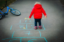 Little Girl Play Hopscotch On Playground