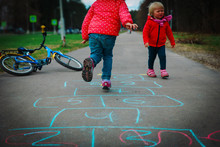 Kids Play Hopscotch On Playground