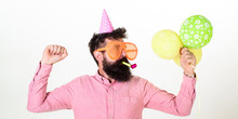 Celebration Concept. Guy In Party Hat With Air Balloons Celebrates. Man With Beard And Mustache On Busy Face Blows Into Party Horn, White Background. Hipster In Giant Sunglasses Celebrating Birthday