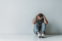 Full Length View Of Scared Depressed Man Sitting With Hands Behind Head On Floor