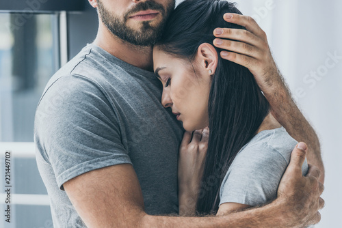 cropped shot of bearded man hugging and supporting young sad woman Fototapet