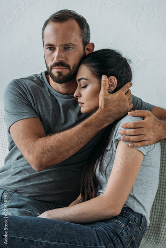 Fotografía bearded man supporting and hugging stressed sad woman sitting on couch