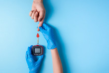 Nurse Making A Blood Test. Man's Hand With Red Blood Drop With Blood Glucose Test Strip And Glucose Meter