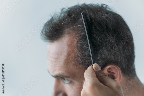 close-up view of mid adult man combing hair with comb isolated on grey, hair los Fototapeta