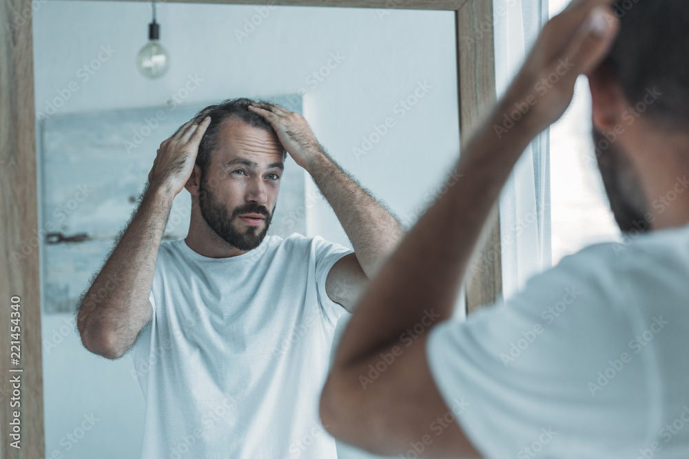 Fototapeta cropped shot of middle aged man with alopecia looking at mirror, hair loss concept
