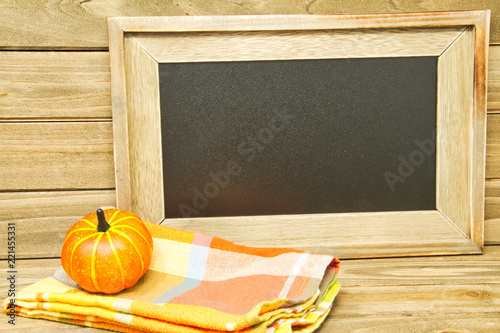 Fotografie, Obraz  A still life of an autumn colored napkin with a pumpkin on a wood table and a chalk board