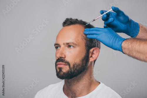 cropped shot of doctor with syringe giving injection to man with alopecia lookin Canvas Print