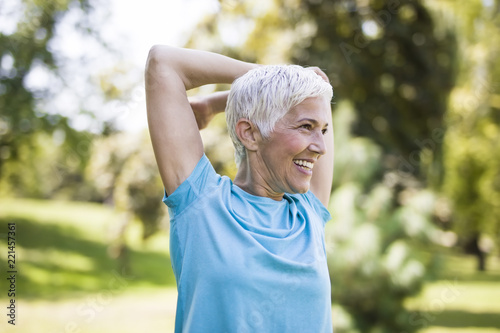 Senior woman doing exercise for stretching hand in the park Fototapeta