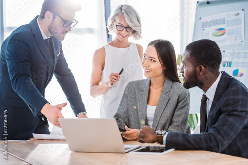 Photo  smiling multiethnic businesspeople working on project in office and looking at l