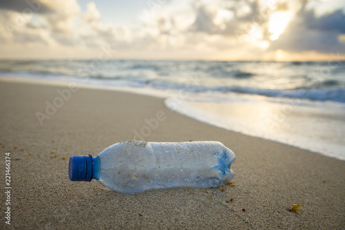 Valokuva  Blue plastic bottle pollution washed up on the beach with stormy seas and sky in