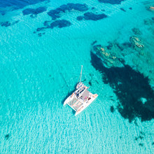 Drone Aerial View Of Catamaran Sailing Boat In Maddalena Archipelago, Sardinia, Italy. Maddalena Archipelago Is A Group Of Islands Between Corsica And North-eastern Sardinia.