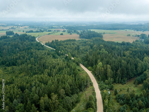 drone image. aerial view of rural gravel road in green forest and trees with shadows from above
