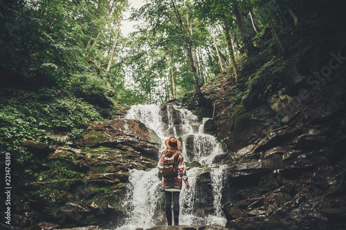 Valokuva stylish hipster girl in hat with backpack looking at waterfall in forest in mountains
